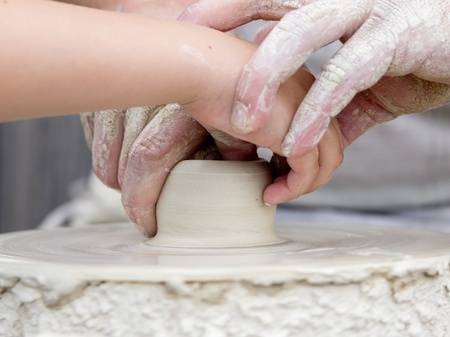 Artisan learning a child to make potter from white clay.