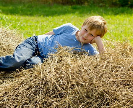 blue jeans kids: Boy have a rest on the haystack.