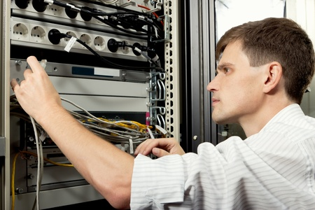 administrators: The engineer stand in datacenter near telecomunication equipment and looking at ethernet path cord.