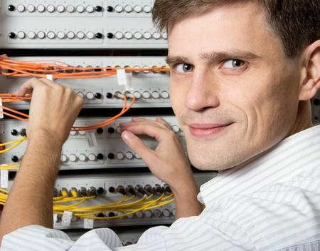 telecoms: L'ingegnere in un centro di elaborazione dati di Internet Service Provider ISP tenere patch cord in fibra