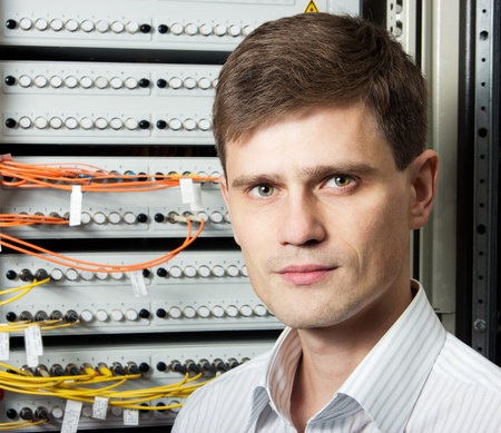 The engineer in a data processing center of ISP Internet Service Provider stand near fiver optic cross box. Фото со стока
