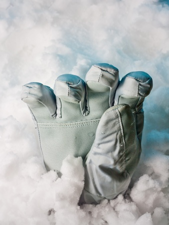Buried alive. Help. Help me. One glove in snowdrift with deep blue shadows.