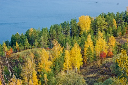 Excellent autumn landscape with yellow, red and green leaves on the trees. The tree line down to the blue river. In the river, the fishermen are fishing from boats. photo