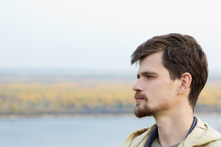 A young man stands in the open air. He wore warm clothing and weatherproof. A man is not clean-shaven. He has a mustache and beard. The man looks away. In the background the river bank and autumn woods with clear skies. The total light is soft. photo