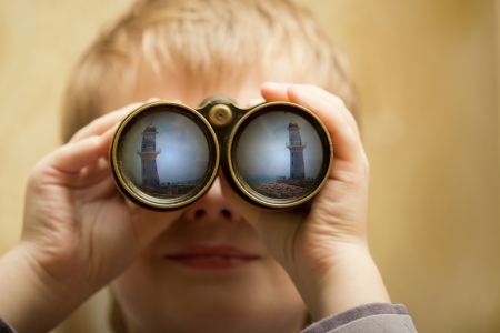 The boy looks through the binoculars and sees a lighthouse in the port. Stock Photo