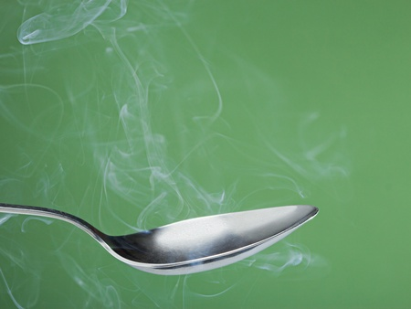 exhalation: Empty metal spoon over green background with steam. Stock Photo
