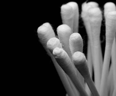 productos de aseo: Macro foto de un bastoncillo de algodón para la limpieza del oído sobre fondo negro.