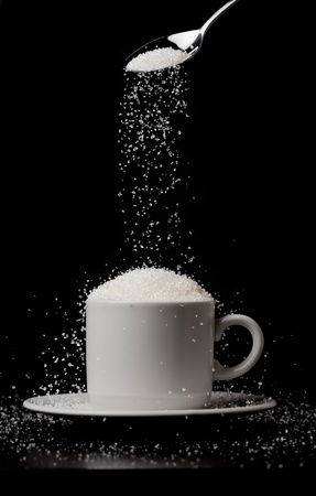 Sugarfall. Чашка кофе с горкой сахара и ложкой. Концепция пристрастие к сахару. Черно-белая фотография.