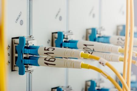 fibra óptica: Router de Internet moderno en el centro de datos con tarjetas de interfaz, módulos 10G XFP y el cable de fibra óptica monomodo de parches en los puertos. Enfoque en el puerto.