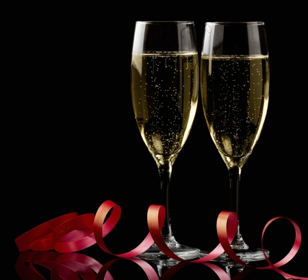 Two glasses with white wine over black background with red ribbon photo