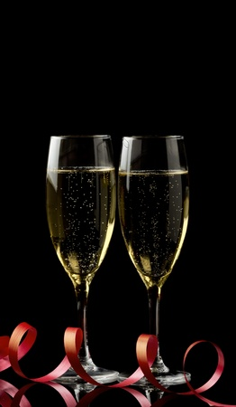 champagne flutes: Two glasses with white wine over black background with red ribbon. Copy-space.