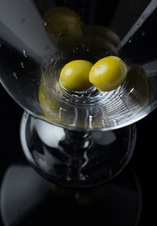 Two green olives waiting when alcohol will fill the glass. Help them. photo