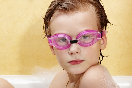 Cute boy have fun in the bathroom. The boy in the foam bath and swimming goggles. photo