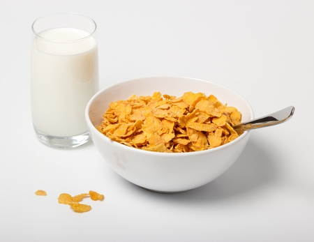 cornflakes: Corn flakes in deep plate with spoon and glass with milk.