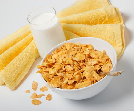 Corn flakes in deep plate with spoon, glass with milk and yellow towel. A breakfast. Stock Photo