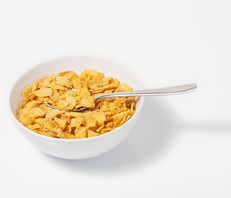 cornflakes: Corn flakes in deep plate with spoon.A Breakfast. High key.