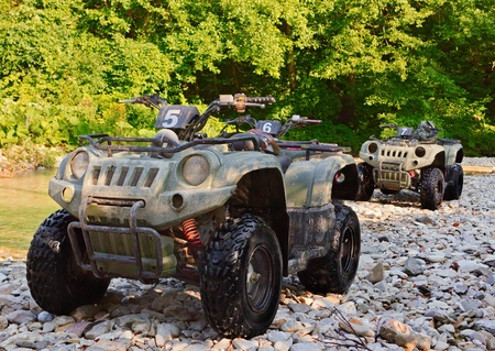 ATVs parked on the shore of a mountain river in the mountains. People are resting somewhere near.