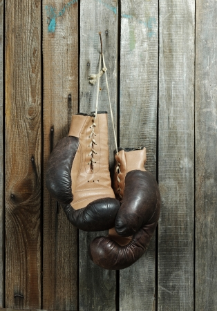 Brown old boxing gloves wooden wall Stock Photo
