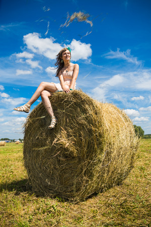 Young woman sit on a newly built hay stack. photo