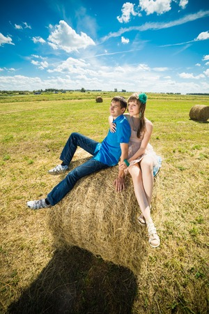 marge: Young couple sitting on a hay stack