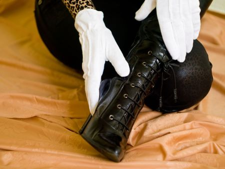 white glove touch black boot on a orange background photo