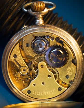 Isolated d clockl mechanism of older scratched, threadbared clock and bolt on the blue background.  photo