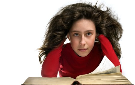 Girl in red cloth with big old book. Here hair is curl. Here hair is flying. She rested his head with his hands.She has a dreamy look photo