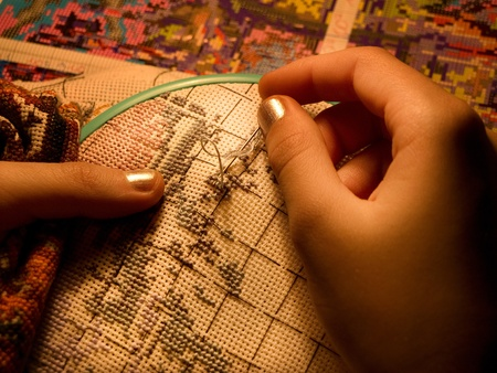 thread count: Low key. Warm light. Embroidery close-up. Childrens hands.