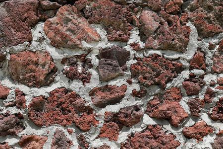 Red volcanic rock wall texture Фото со стока