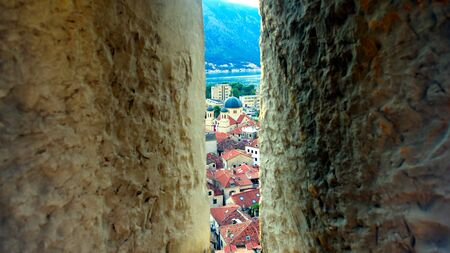 Kotor, Montenegro Panoramic view across the beautiful Bay of Kotor and the Old Town at sunset trrough loophole