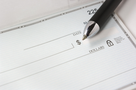 A pen resting on a blank check. photo