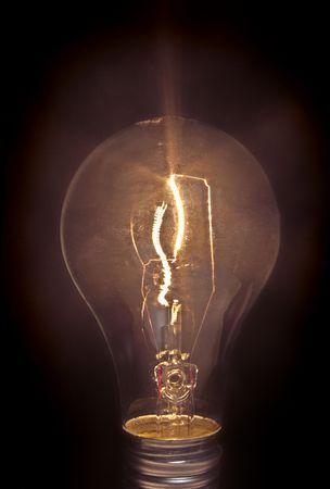 incandescent: Lit up incandescent light bulb on black.