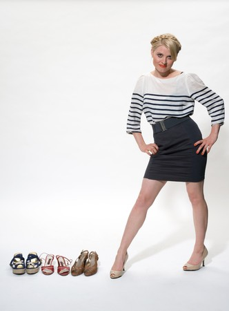 young blond posing alongside 3 pairs of shoes photo