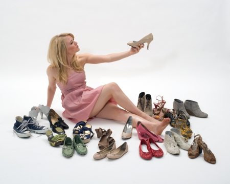 varieties: happy young blond woman sitting on the floor surrounded by shoes Stock Photo
