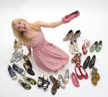 be the identity: happy young blond woman sitting on the floor surrounded by shoes Stock Photo