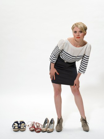 be the identity: young blond posing alongside 3 pairs of shoes