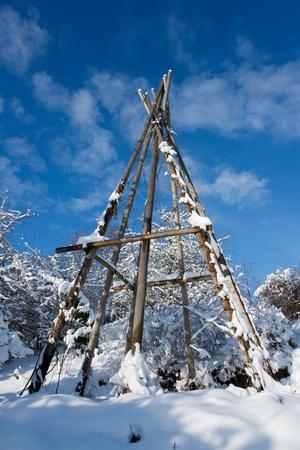 tepee: snowy framework of a tepee tent under blue sky Stock Photo