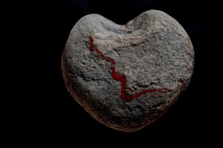 heartsickness: heart-shaped stone with a bloody disruption in front of a black background
