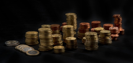euro coins: a lot of different high stacked heaps of Euro coins