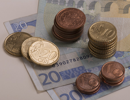 euro bill: Euro coins stacked on 20 Euro bills and a 5 Euro bill.