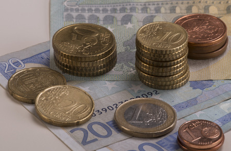 Euro coins stacked on 20 Euro bills and a 5 Euro bill. photo