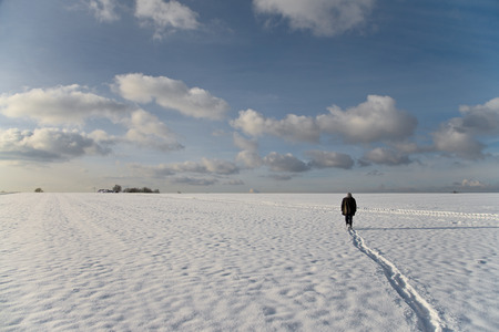 take time out: a man in a leather jacket is walking pensively on a big bright white snowy field
