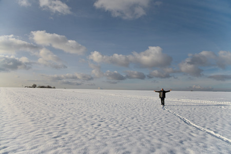 take time out: a man standing on a bright snowy high plateau with wide outstretched arms looking to heaven Stock Photo