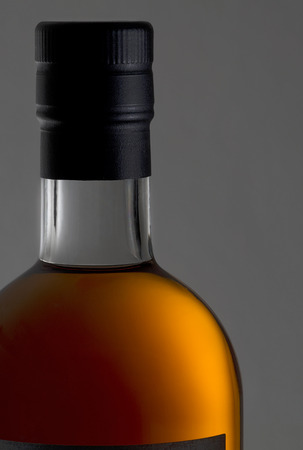 shrink: detail of a bottle of cognac - bottleneck, cork closure with black shrink capsules and golden cognac. Stock Photo