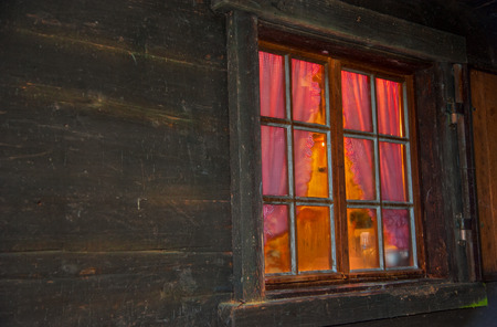gathered: Atmospherically exterior shot of a log cabin with a window with glazing bars in the evening.  Inside behind gathered curtains in red and orange colors is a warm atmosphere in the room.