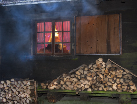 fume: Atmospherically exterior shot of a log cabin with a window with glazing bars in the late evening. Inside behind gathered curtains in red colors is a warm atmosphere in the room. Blue fume from the outside chimney comes down from the roof.  Under the windo Stock Photo