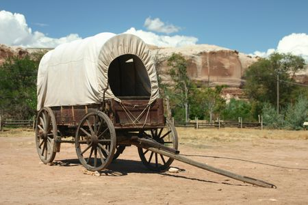 covered wagon standing in sand with rock formations in the background. Real wild west scene