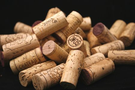 a bunch of different wine bottle corks on a black background