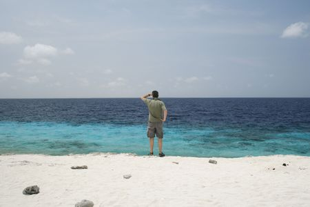 far away look: man stands at ocean shore and gazes at horizon Stock Photo