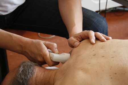 electronical: Physiotherapist treatment on shoulder of senior patient Stock Photo